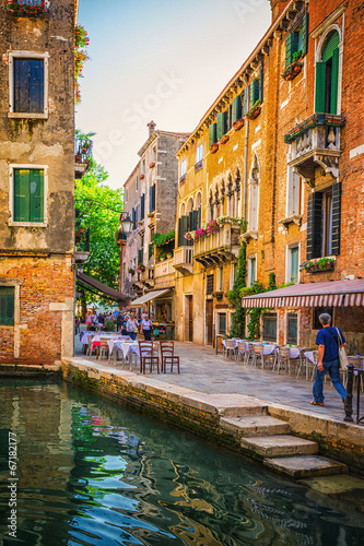 Obraz na Szkle Narrow canal among old colorful brick houses in Venice