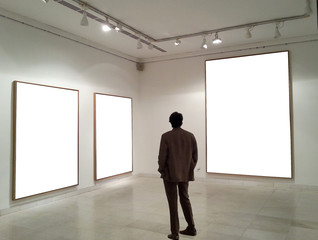 Man in gallery room looking at empty frames