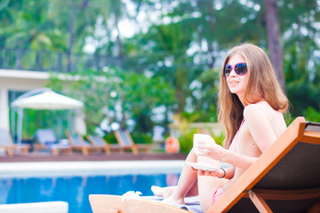 long haired yound woman in bikini on chaise lounge luxury pool