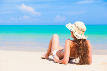 woman in straw hat lying on tropical beach