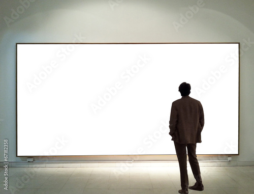 Man in gallery room looking at empty frames - 67182358
