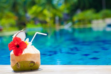 exotic fresh coconut shake and flower by the tropical pool