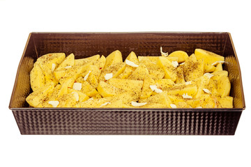 Raw peeled potatoes with spices and butter in tray