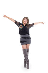 latin girl wearing dress and boots posing with arms open