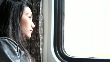 Young woman look from window while traveling by train