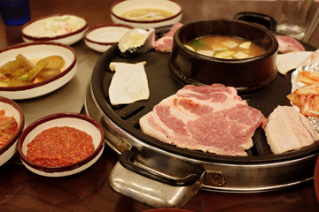 Cooking pork barbecue at the table in Korean restaurant