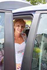 attractive caucasian bride sitting in car