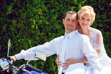 beautiful young wedding couple on motorcycle