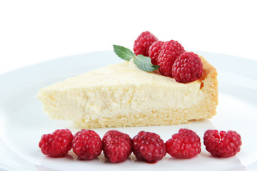 Slice of cheesecake with raspberry on plate, isolated on white