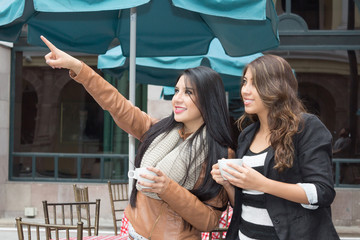 two young girls holding cups of coffee pointing a place