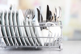 Fototapety Clean dishes drying on metal dish rack on light background