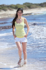 Beautiful young woman walking on the beach