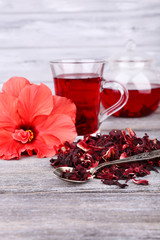 Hibiscus tea in glass teapot and flower