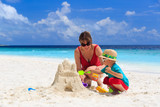 Fototapety mother and son building castle on the beach