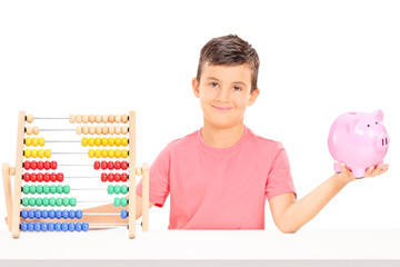 Boy holding a piggybank seated at a table with an abacus