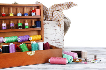 Colorful threads for needlework in wooden box close up