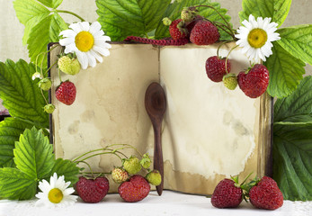 Cook book with strawberries and flowers