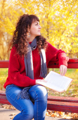 Girl with book in sunny autumn park