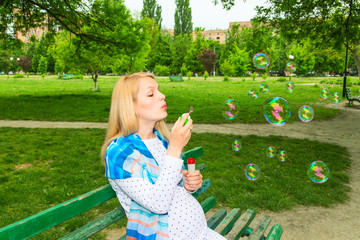 Pregnant park blowing bubbles