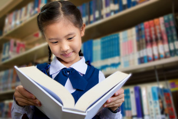 Asian little student in library