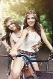 Two boho girls riding a bike poster