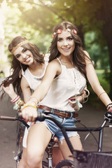 Two boho girls riding a bike