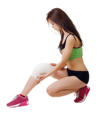 Athletic young woman with elastic bandage on his leg. Isolated
