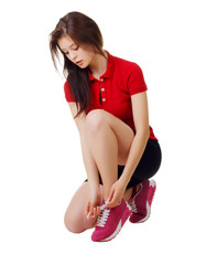 Sporty girl sitting tying shoelaces.white background.