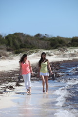 Two women walking barefoot along the seashore