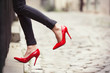 canvas print picture - Woman wearing black leather pants and red high heel shoes