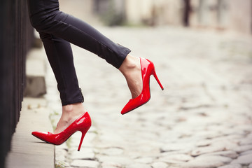 Woman wearing black leather pants and red high heel shoes