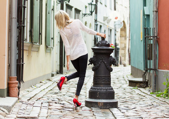 Fashionable woman wearing red high heel shoes in old town