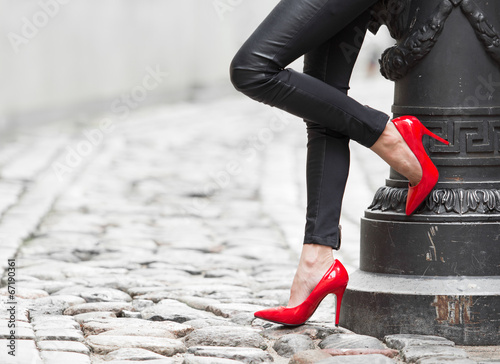 canvas print picture Sexy legs in black leather pants and red high heel shoes