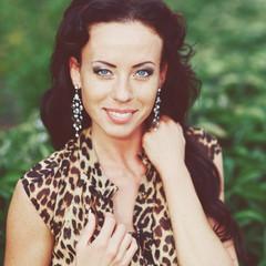 young beautiful brunette in a leopard dress outside