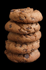 Stack of chocolate chip cookies isolated on black.