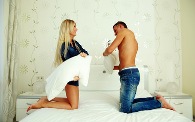 Couple fighting together with pillows in bed