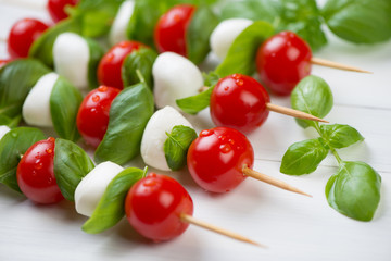 Kebabs with tomatoes, cheese and basil over white wooden surface
