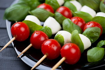 Red tomatoes, mozzarella and green basil on skewers, close-up