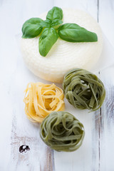Round cheese, green basil and colored tagliatelle, vertical shot