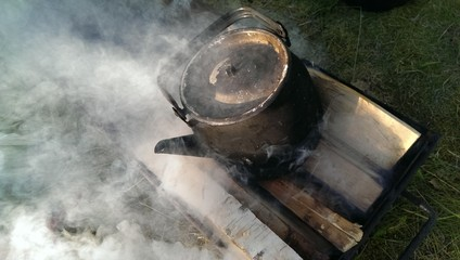 Black metal touristic teapot boiling on an outdoor fireplace
