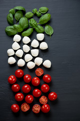 Italian cooking ingredients, black wooden surface, above view