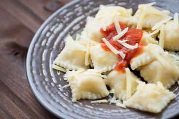 Glass plate with ravioli, tomato sauce and parmesan, studio shot