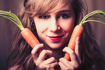 Beautiful young brunette woman as easter bunny with carrots