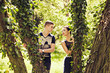 Playful couple behind trees in park