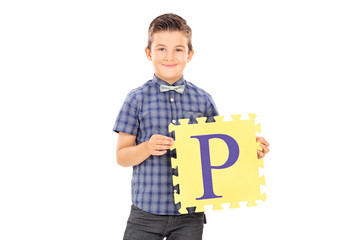 Male kid holding a piece of a puzzle