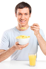 Man eating cornflakes and drinking orange juice