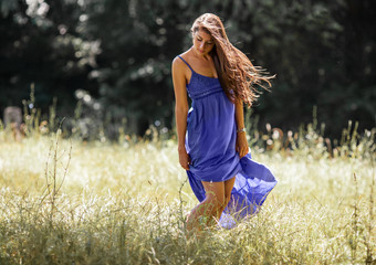 Attractive female model in blue dress.She walking trough meadow.
