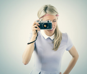 Young woman taking selfie with old film camera