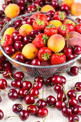 fresh berries and fruits in metallic basket on wooden surface