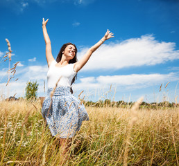 Attractive happy woman joying in beautiful summer day.